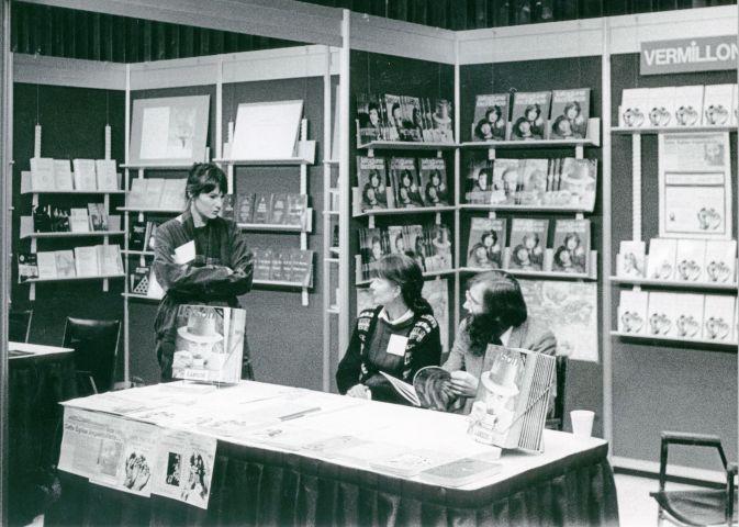 """Photographie en noir et blanc d'un homme et d'une femme d'âge moyen assis à une table devant un étalage de livres. Debout à côté d'eux, une femme plus jeune. Surplombant le kiosque, un panneau avec les mots: """"L'EDITION FRANCO-ONTARIENNE 461."""""""