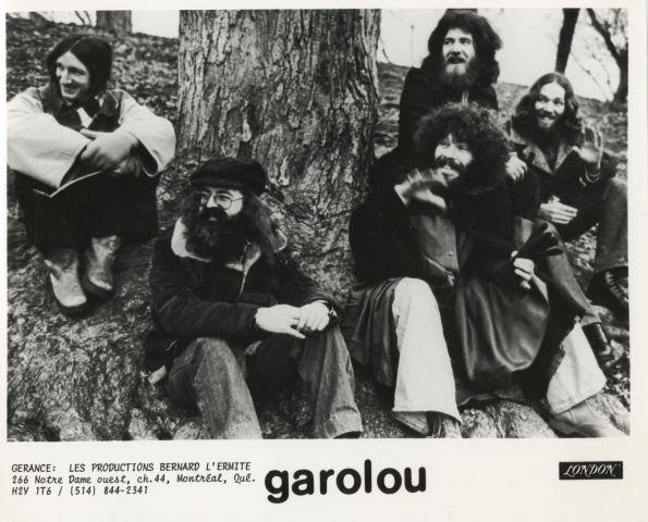 Photographie en noir et blanc avec texte imprimé, en français. Cinq hommes d'âge moyen aux cheveux longs, portant des manteaux et des vêtements décontractés, sont assis au pied d'un arbre. Au bas de la photo, le nom du groupe et les renseignements de la gérance.