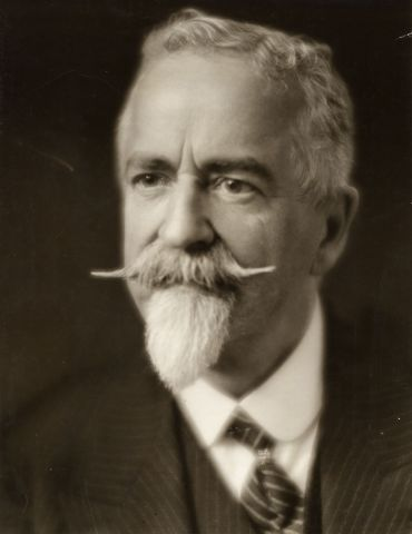 Black and white studio photograph, three-quarter view, of an elderly man with white hair, beard and mustache. He wears a white shirt, and pin-striped suit and tie, looking very distinguished.