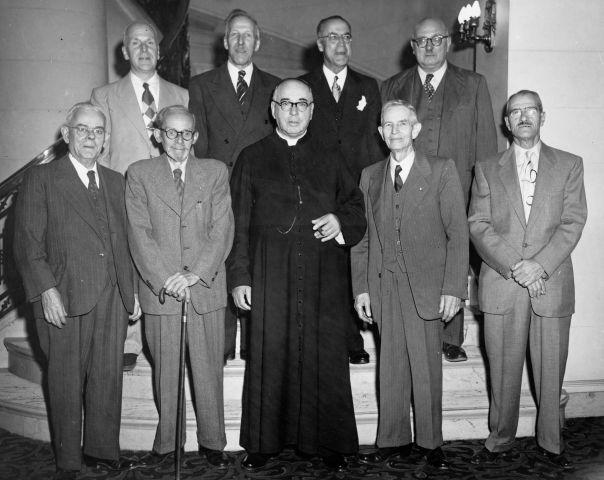 Photographie en noir et blanc de neuf hommes d'un certain âge. Quatre hommes sont debout sur la deuxième marche d'un escalier; cinq hommes sont debout devant eux. Huit des hommes sont vêtus en costume-cravate. L'homme au centre est vêtu d'une soutane noire et il tient un cigare.