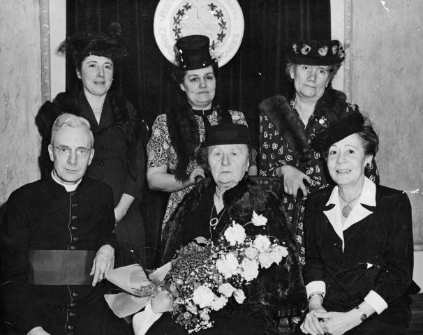 Photographie en noir et blanc d'un groupe de femmes, d'âges divers, accompagnées d'un religieux. Toutes les femmes portent des chapeaux et des robes. Une seule n'a pas d'étole de fourrure. Deux femmes sont assises, dont l'une tient une gerbe de fleurs. Le religieux est assis à leur droite. Les trois autres femmes sont debout derrière eux.
