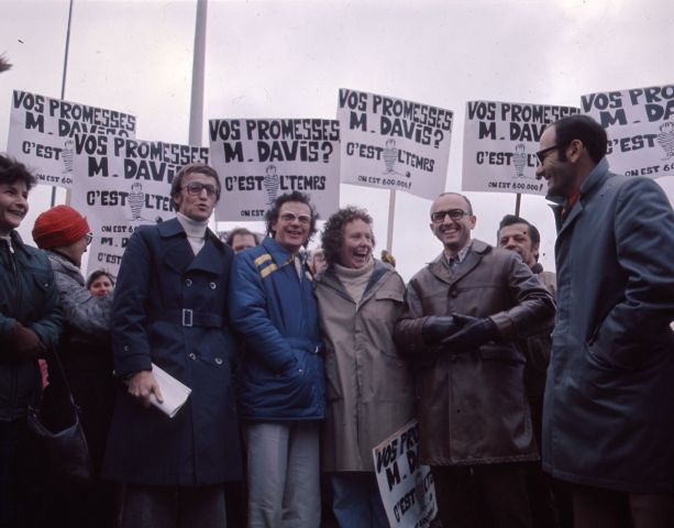 """Colour photograph of five middle-aged people – four men and a woman – in front of a group of demonstrators. They smile and hold placards which read, """"Vos promesses, M. Davis ? C'est l'temps. On est 600 000 !"""" (Your promises, Mr. Davis? It's time. There are 600,000 of us!)."""