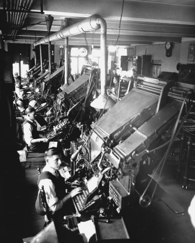 Black and white photograph of five men in a shirt, vest and tie in an industrial workshop. They sit in front of imposing machines of composition, with keyboard.