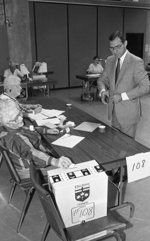 Photographie en noir et blanc d'un homme d'âge mûr en costume-cravate.  Il porte des lunettes. Il est debout devant un bureau de vote tenu par deux femmes du troisième âge. L'une d'entre elles dépose un bulletin de vote dans la boîte de scrutin. À l'arrière-plan, d'autres bureaux de vote.
