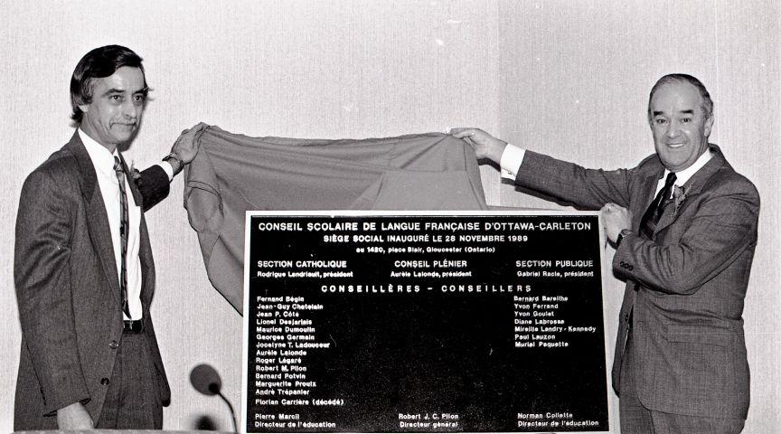 Photographie en noir et blanc de deux hommes d'âge mûr  en costume-cravate, dévoilant une plaque commémorant l'inauguration du Conseil scolaire de langue française.