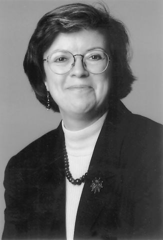 Black and white photograph of a woman smiling at the camera. She has short dark hair, and she is wearing glasses, earrings, and a pearl necklace with a black jacket and white turtleneck.