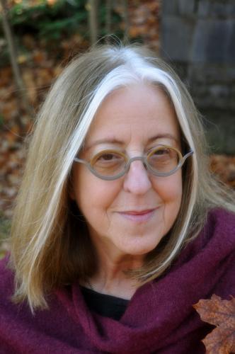 Photographie en couleur, prise à l'extérieur en automne, d'une femme d'âge mûr. Elle a les cheveux poivre et sel mi-longs. Elle porte des lunettes et une écharpe violette.  Elle sourit à la caméra.