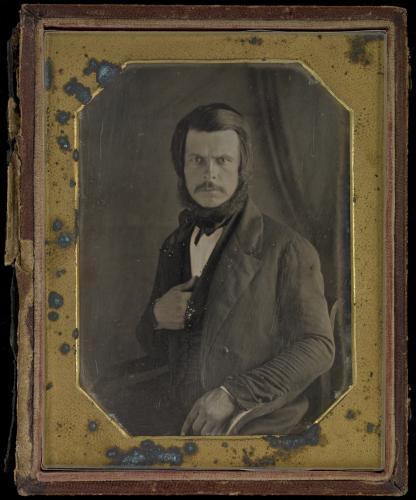 Photographie en noir et blanc, prise en studio, d'un homme à moustache au regard perçant, habillé d'un costume trois-pièces. Son bras gauche repose sur le bras du fauteuil où il est assis, et sa main droite est placée sous son gilet. La photographie est insérée dans un cadre doré, fortement abîmé.