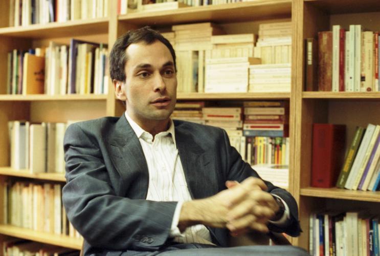 Photographie en couleur d'un homme d'âge moyen, vu de trois quarts. Il est assis, les mains jointes devant lui. Il a les cheveux bruns et la peau basanée. Il porte un costume sans cravate. À l'arrière-plan, une bibliothèque.