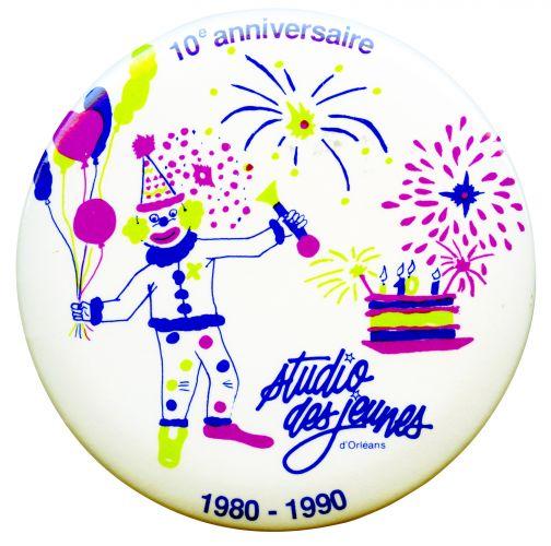 Photographie d'un bouton erprésentant un clown qui tient des ballons, un gâteau d'anniversaire and des feux d'artifice. En bleu, vert clair et fushia, sur fond blanc. Un logo bleu apparaît au bas du macaron, ainsi que la mention de l'anniversaire.