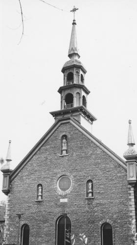Photographie en noir et blanc d'une église en brique, surmontée d'un clocher et de deux tourelles. La façade de l'église compte trois portes, un œil-de-bœuf ainsi que trois statues.