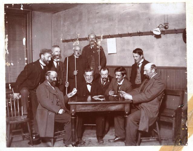 Photographie en noir et blanc d'un groupe d'hommes autour d'une table. Cinq hommes dont un religieux sont debout, tenant à la main, pour certains d'entre eux, une queue de billard et cinq hommes sont assis. Parmi ceux-ci, deux hommes ont des cartes dans les mains. La photographie est légèrement abîmée.