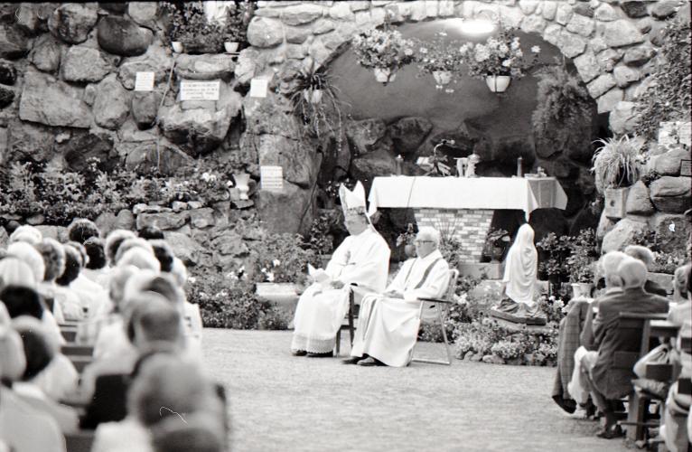 Photographie en noir et blanc d'un évêque et d'un prêtre vêtus de blanc assis devant une grotte décorée de fleurs et d'une effigie de la Vierge. De nombreux fidèles, vus de dos, sont assis sur de longs bancs ordonnés en rangées.